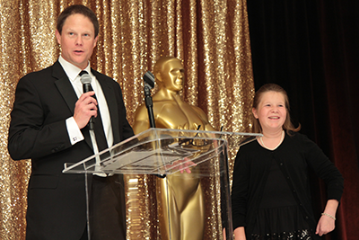 Left to right: Keith Sultemeier, Chairman of the Credit Union for Kid's Wine Auction and CEO of Kinecta FCU, speaks to wine auction attendees with Jadyn Skorpanich at his side. Jadyn, 11, is a Children's Miracle Network Hospital patient at Rady Children's Hospital San Diego.