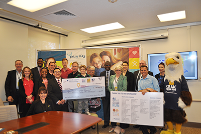 """Representatives from credit unions, the California and Nevada Credit Union Leagues, UC Davis Children's Hospital, Credit Unions for Kids, and local leaders pose with a check for more than $580,000 on behalf of Credit Union Miracle Day and the """"Family of Races,"""" representing the total funds raised for children's hospitals nationwide."""