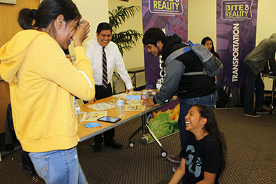 Left to right: Arroyo Valley High School students Lizbeth Cruz, 14, and Cindy Alvarez, and Thinkwise CU Lending and Compliance Manager Arnold Ramirez react to Lizbeth being hit with an unexpected expense and winding up with only $15 left in her checking account during Bite of Reality, a financial reality program held at Cal State San Bernardino March 23 for ninth-graders from various San Bernardino high schools.